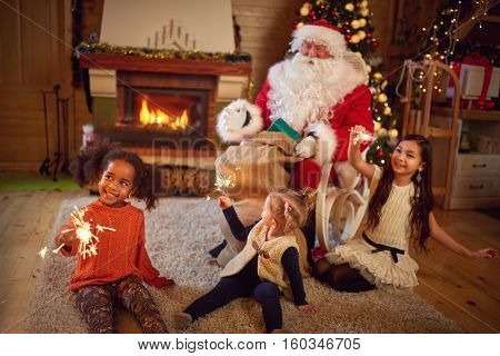 Three girls playing with Christmas sprinklers with Santa Claus in Christmas atmosphere