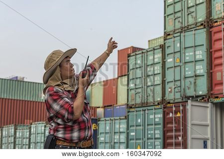 supervisor checking containers data and talking radio.