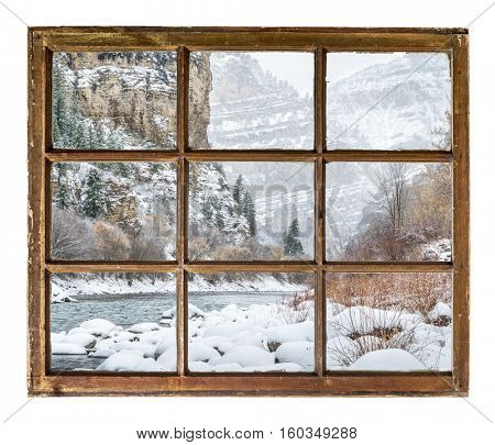Winter scenery of mountain river in deep canyon as seen  through vintage, grunge, sash window with dirty glass