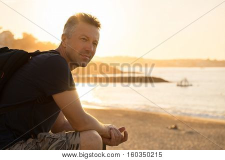 Handsome man. Outdoor male portrait. Middle-aged man resting at the beach, summer outdoor portrait, image toned. Saint Jean de Luz, France.