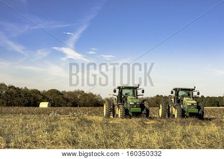 Prattville Alabama USA -- November 5 2016: Two John Deere tractors sitting in front of a harvested cotton field in Alabama.