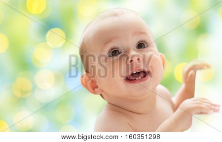 childhood, babyhood, emotions and people concept - happy little baby boy or girl looking up over green holidays lights background