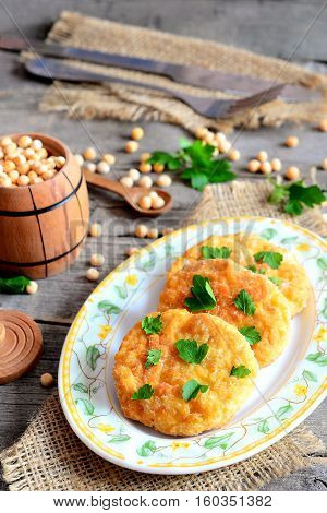 Fried pea patties on a plate. Spicy vegan patties cooked from yellow dried peas and decorated with parsley. Fork, knife, small decorative barrel on an old wooden background. Vegan food recipe. Closeup