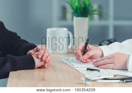 Woman patient applying for medical exam at female doctor's office general practitioner writing notes in health history record document