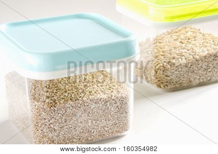 Food storage. Food ingredients (cut wheat and wild rice) in plastic containers. Selective focus.