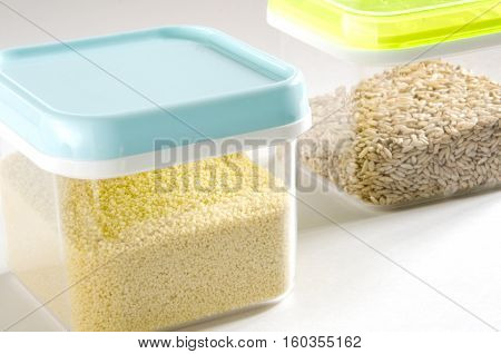 Food storage. Food ingredients (cous cous and wild rice) in plastic containers. Selective focus.