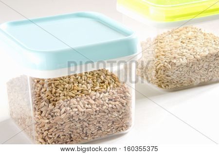 Food storage. Food ingredients (spelt wheat and wild rice) in plastic containers. Selective focus.