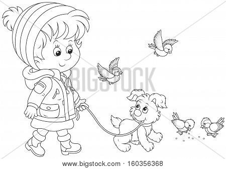 Little girl in a winter jacket and a warm hat and mittens walking with a small pup