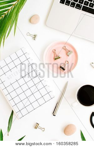 Flat lay top view office table desk. Workspace with notebook laptop palm branch coffee cup scissors and clips on white background.