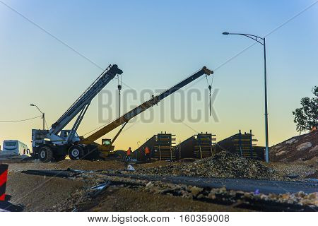 Two engineers observed as a group of cranes proceed to move a structure for the construction of a road bridge