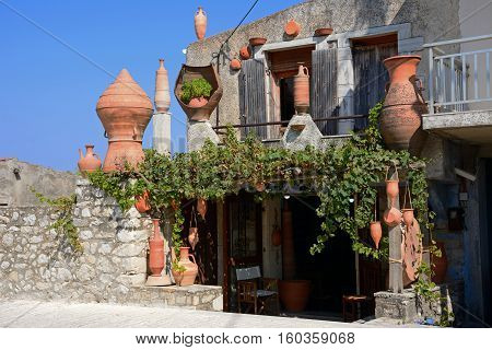 Ceramic workshop with large pots outside in the village centre Margarites Crete Greece Europe.