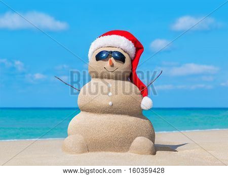 Happy sandy snowman in Christmas Santa Claus hat at sunny ocean beach New Year holiday destinations concept for travel to hot south countries