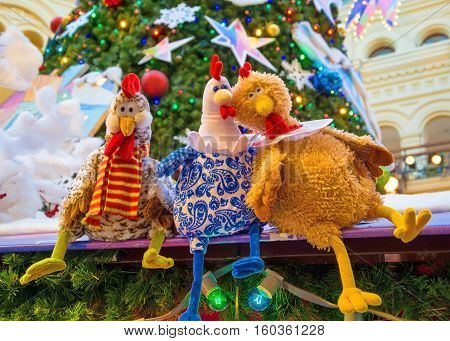 RUSSIA, MOSCOW. NOVEMBER 23, 2016 Funny toys - colorful roosters are a symbol of 2017. These stuffed animals decorate the fairground festive showcases in Moscow.