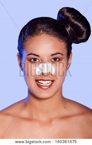 Young smiling woman with nosestrips on nose