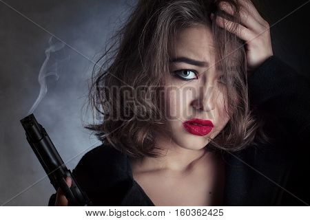 scared beautiful girl with gun holds her head on black background, toned image