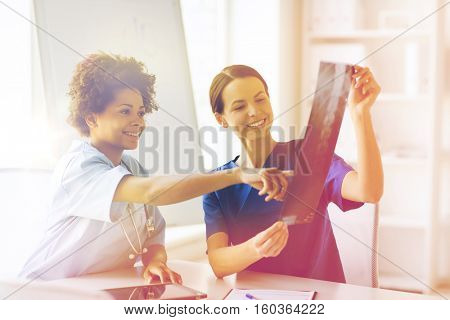 radiology, surgery, people and medicine concept - happy female doctors looking to and discussing x-ray image at hospital