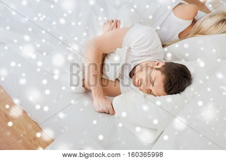 people, relationship difficulties, conflict and family concept - couple sleeping in bed at home over snow