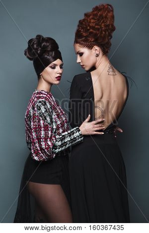Beautiful girls in evening dress with avant-garde hairstyles. Beauty the face. Photos shot in the studio.