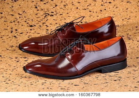 Classic shiny brown mens shoes standing on a sheet of balsa wood