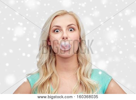 emotions, expressions and people concept - happy young woman or teenage girl chewing gum over snow
