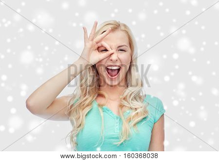 fun, emotions, expressions and people concept - smiling young woman or teenage girl making ok hand gesture over snow