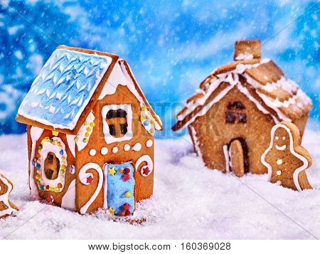 Two gingerbread houses and gingerbread man next to them in the snow. Village Christmas gingerbread houses in the winter background.
