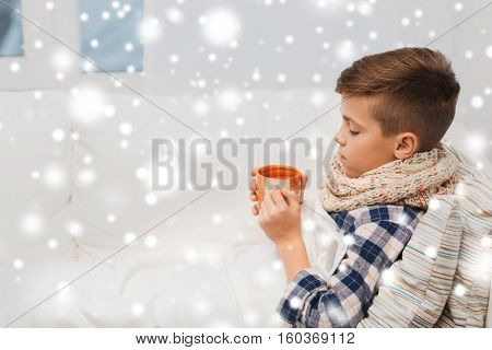 childhood, healthcare, people and medicine concept - ill boy with flu lying in bed and drinking tea at home over snow