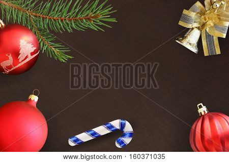 Christmas fir branch stick red wavy and dull ball and bell on a dark background