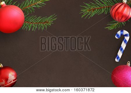 Christmas tree branch with stick pink and red wavy dull ball on a dark background. Top view.