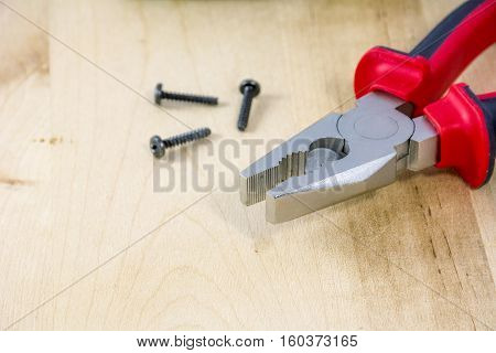 Pincers with screws on light wooden background