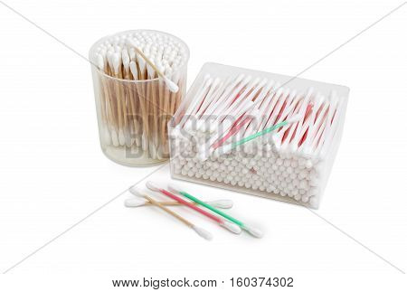 Cotton swabs on a white red and green plastic rods in rectangular plastic container cotton swabs on a wooden rods in round plastic container and several cotton buds separately on a light background