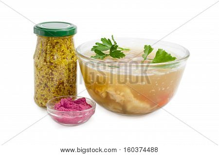 Pork aspic in transparent glass bowl beet horseradish sauce in small glass French mustard in small glass jar on a light background