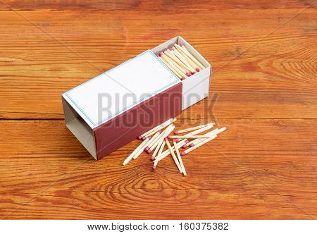 Household safety matches made from wood in large cardboard matchbox and several matches beside on a surface old wooden planks