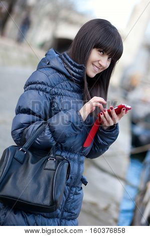 Happy beautiful brunette tourist in Paris sending an sms to someone poster