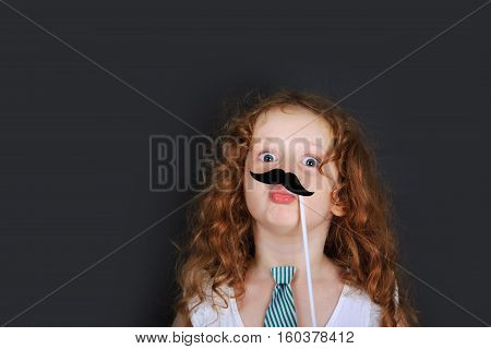 Funny little girl hold carnival mustache and send air kisses. Father day concept.