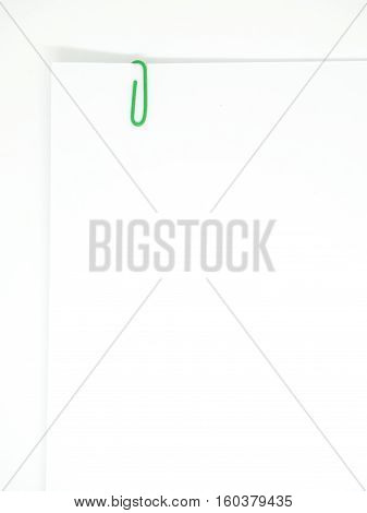 Green Paperclip Attached On White Paper Isolated
