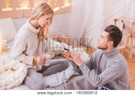 Romantic proposal. Loving attractive brunette man showing an engagement ring and making a proposal to his girlfriend while expressing his love to her