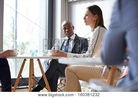 Young businessman with colleagues having coffee in office