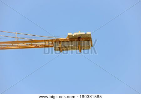 Close-up counterweight of the crane on blue sky background.