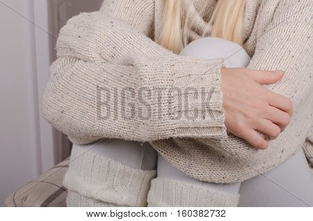 Closeup of girl's hands in casual wool sweater hugging her knees to her chest feeling lonely