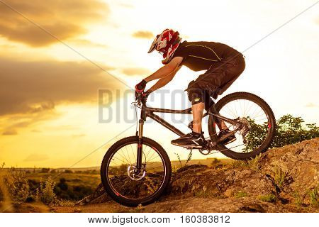 Professional Cyclist Riding the Bike Down Rocky Hill at Sunset. Extreme Sport Concept. Space for Text.
