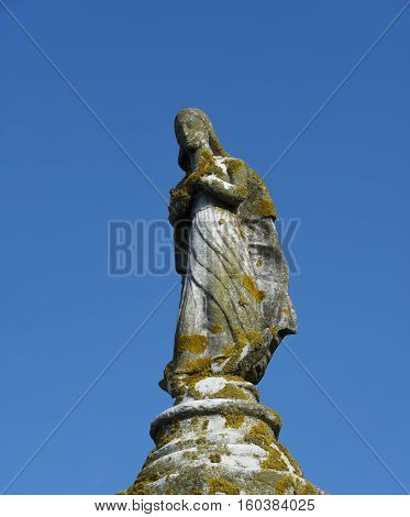 Medieval statue of a saint on an ancient column with lichen in the Island of Torcello near Venice