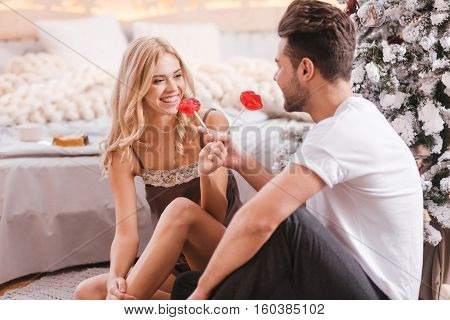 For my girlfriend and me. Handsome brunette young man holding lollipops and giving one of them to his girlfriend while sitting under the Christmas tree