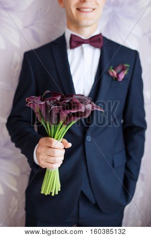 Gorgeous smiling groom. andsome groom at wedding tuxedo smiling and waiting for bride.Elegant man in black costume and bow-tie.