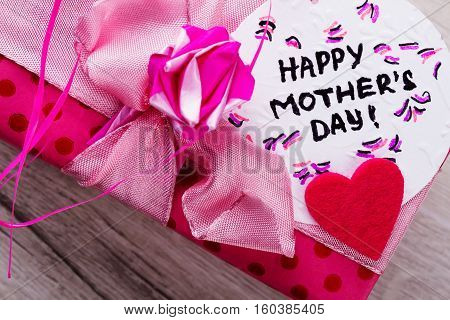 Happy Mother's Day card inscription. Pink bow on gift box. Greeting handmade composition. Send best wishes.