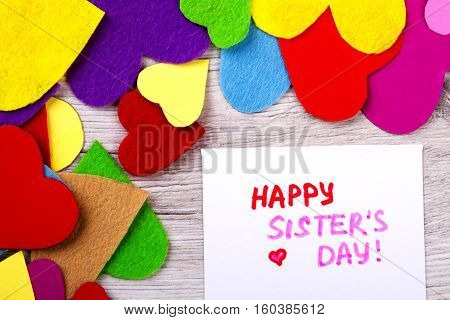 Greeting card on Sister's Day. Bright hearts on wooden background. Congratulate your sister. Warm family relationships.