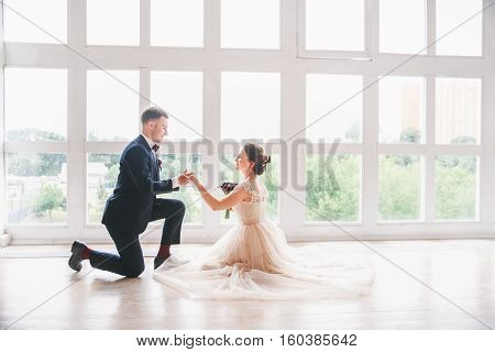 wedding couple  on the studio. Wedding day. Happy young bride and groom on their wedding day. Wedding couple - new family.Man kissing his wife's hand