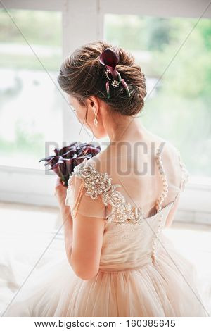Beautiful charming bride in a luxurious dress looking up.Portrait Of Happy Bride Sitting in wedding dress in a white photo Studio. Young attractive bride with flowers