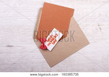 Mother's Day enveloped greting card. Small bow tie on card. Use old-fashioned way of congratulation. Provide festive mood for mom.