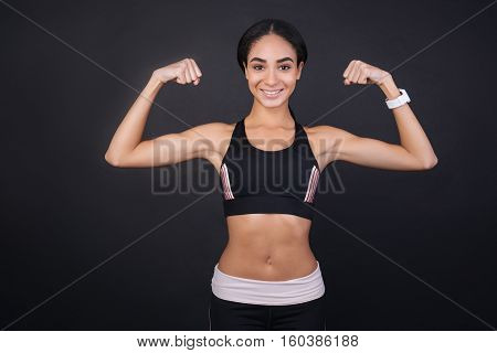 Be in good shape. Happy smiling sportswoman wearing sport watches on the left hand looking straight at camera standing isolated over black